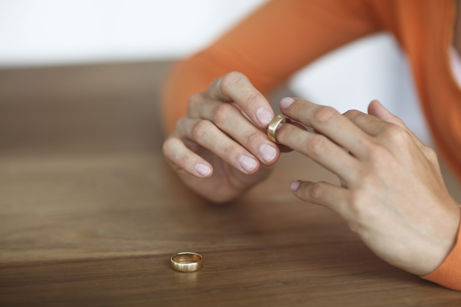 Mid adult woman toying with gold wedding ring on finger